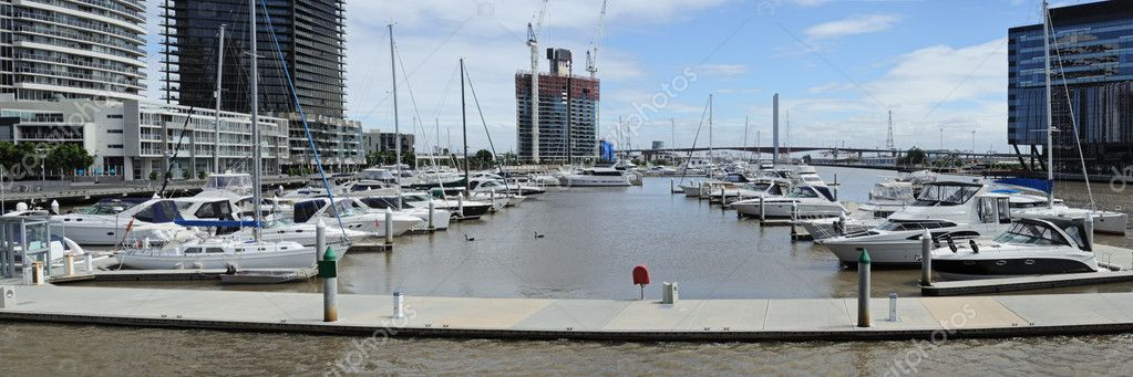 Panorama of berth with many sailing yachts and powerboats at Yarra river on sunny day in new business area in Melbourne with Bolte Bridge and constructed skyscraper in background — Stock Photo #9634276