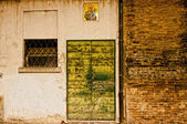 Textured old door and holy picture on wall in Reggio Emilia, Italy — Foto Stock