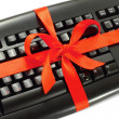 Computer keyboard with red bow - Stock Photo