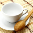 White cup with wooden spoon — Stockfoto