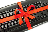 Computer keyboard with red bow — Stock Photo