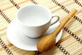 White cup with wooden spoon — Stock Photo