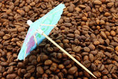 Cocktail umbrella on a coffee beans — Stock Photo