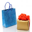 Shopping bag and gold present — Stock Photo