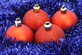 Red Christmas balls with blue tinsel — Stock Photo