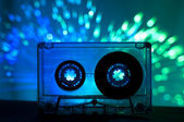 Transparent Cassette tape and disco light background — Stock Photo