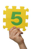 Children hand holding the number Five. White isolated number — Stock Photo