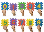 Children hands holding numbers. White isolated multicolor number — Stock Photo