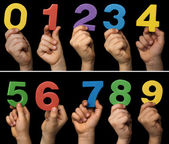 Children hands holding numbers. Black isolated multicolor number — Stock Photo