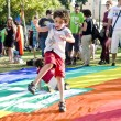 Boy dancing on the rainbow flag — Stock Photo