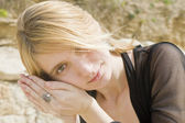 Blonde girl listening to a shell — Stock Photo