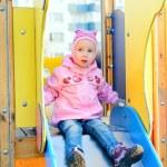 Child girl sitting on slide in playground. — Stock Photo #10324330