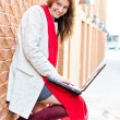 Portrait of pretty girl with laptop on the background of the city - Stock Photo