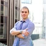 erfolgreichen Mann mit Stadt im Hintergrund verschränkten Armen — Stockfoto