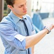 Successful man looking at his watch. Over urban background. — Stock Photo