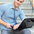 Young guy with a laptop sitting on the stairs — Stock Photo