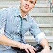 Young guy with a laptop sitting on the stairs - Stock Photo