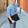 Young guy posing with a laptop on the street. - Stock Photo