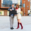 Girl with a guy standing on the street and look at the laptop - Stock Photo