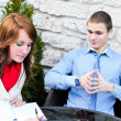 Business partners meeting: Male and female sitting outdoors. Focus on female. — Foto Stock