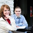 Business partners meeting: Male and female sitting outdoors. Focus on female. — Stock Photo