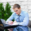 Businessman with laptop in cafe on the street. Makes notes with pen - Stock Photo