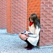 Female sits and reads a book at the wall — Stock Photo