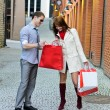 Smiling female shows purchases to male - Stock Photo