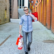 Portrait of handsome male with shopping bags - Stock Photo