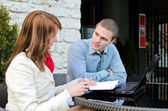 Business partners meeting: Male and female with laptop sitting outdoors — Stock Photo