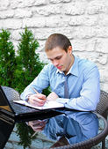 Businessman with laptop in cafe on the street. Makes notes with pen — Stock Photo