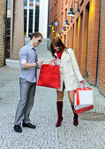 Smiling female shows purchases to male — Stok fotoğraf
