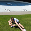 Runner at the city stadium warming and stretching — Stock Photo