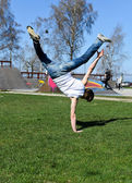 Breakdancer doing a flip on the grass. — Stock Photo