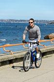 Portrét pohledný muž, jezdit na kole u moře — Stock fotografie