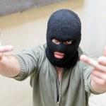 Burglar wearing a mask shows fuck gesture. — Stock Photo
