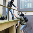 Stock Photo: Escape from robbery. One tries to help another to climb rails.