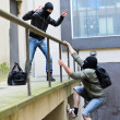 Escape from a robbery. One tries to help another to climb the rails. — Stock Photo #10501913