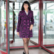 Pretty woman in a coat going thru revolving doors — Stock Photo