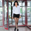 Pretty woman going thru revolving doors — Stock Photo