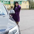 Pretty woman in a coat sits in an expensive car — Stock Photo