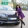 Pretty woman posing near expensive car — Stock Photo