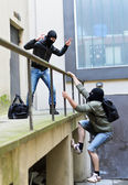 Escape from a robbery. One tries to help another to climb the rails. — Stock Photo