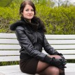 Attractive girl sitting on a park bench — Foto Stock