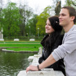 Cute couple looking at a pond in the park — Stock Photo