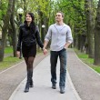 Couple walking down the road in the park. — Stock Photo