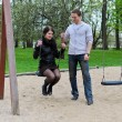 Guy rolls a girl on a swing in the park. — Stock Photo