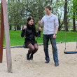 Stock Photo: Guy rolls a girl on a swing in the park.