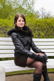 Attractive girl sitting on a park bench — Stock Photo