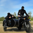 Two armed men riding a motorcycle with a sidecar. Motion blur. — Stock Photo